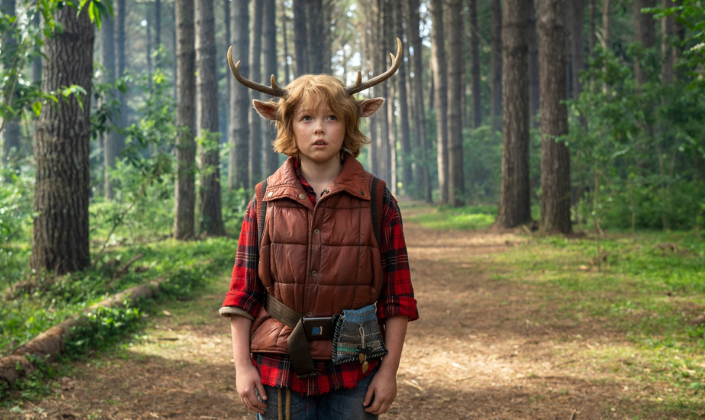 Imagem de capa: cenário de uma floresta na qual vemos um garotinho com uma camisa vermelha de flanela quadriculada, um colete marrom por cima, os cabelos crescidos e um par de chifres de cervo crescendo a partir dos lados da cabeça.