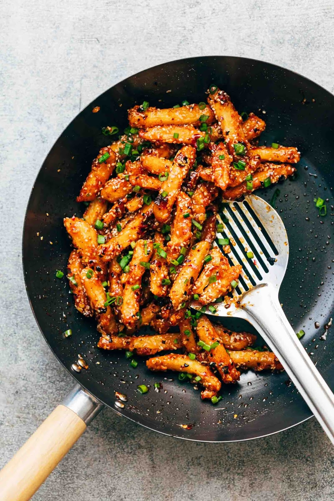 Crispy Honey Chilli Potatoes are a super addictive snack - fried potato fingers are tossed in a sesame honey chilli sauce that's sweet and spicy and will give you sticky fingers that you'll be licking to get every last bit of sauce!