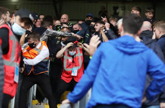 Image of a Turf Moor stadium employee struggling to escape the chaotic crowd.