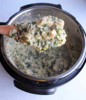 spoonful of steaming hot spinach chicken risotto being lifted out of the pot