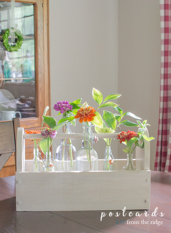 wooden toolbox with colorful flowers in glass bottles