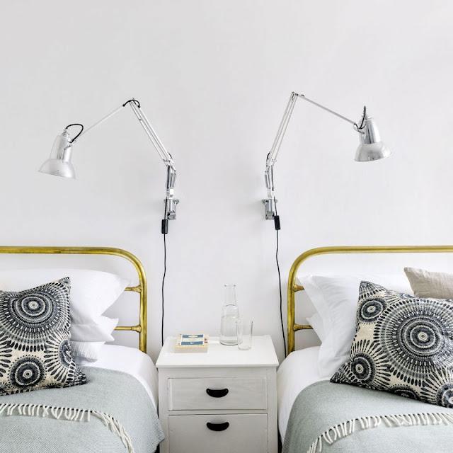 Kamar tidur twin dengan lampu samping tempat tidur yang terpasang di dinding dan meja samping bersama