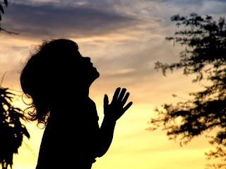Em atitude devocional, criança entrelaça dedos das mãos, olha para o céu e ora. Cenário ao ar-livre, apresentando o céu em cores amarela, vermelha e roxa.