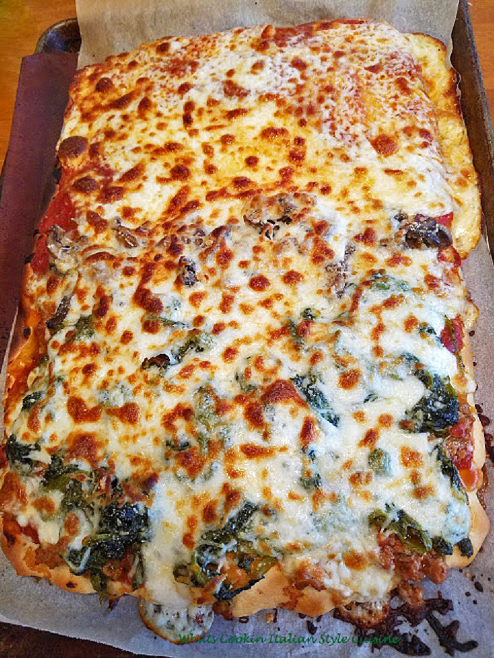 This is a homemade pizza dough topped with sausage and broccoli rabe with tomato sauce and browned mozzarella cheeses on top