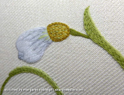 Trellis on top of crewel snowdrop flower bud stitched in different shades of gold and green