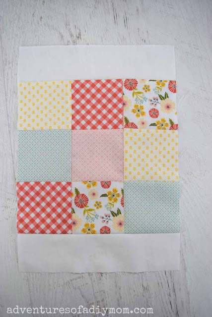 white border along the top and bottom of a nine patch quilt block