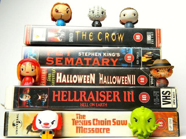 A photo showing a pile of Horror VHS movies, with tiny horror character figures sitting on top of them