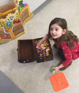 Little girl going through a treasure chest of goodies