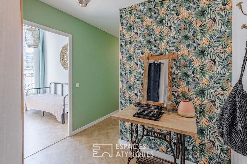 Hall con pie de máquina de coser y papel pintado tropical.