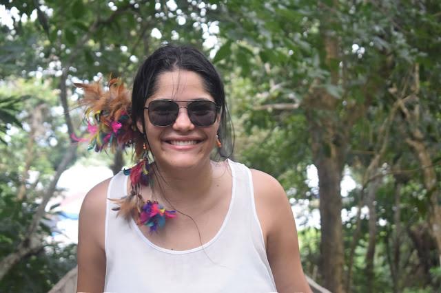 menina sorrindo em meio a selva