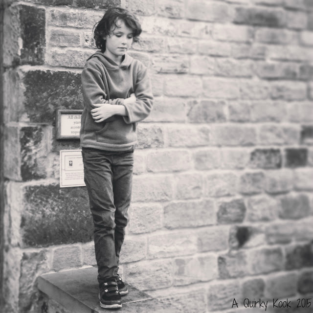 Boy stood on a wall in black and white