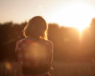 Eine junge nachdenkliche Frau unter einem Sonnenuntergang