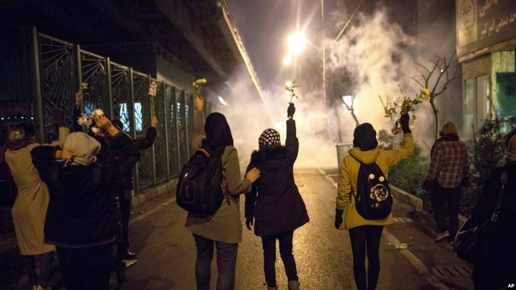 Manifestantes frente a la Universidad Amir Kabir en Teherán levantan flores mientras la policía dispara gas lacrimógeno / AP