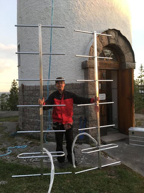 Mies piteelee kahta noin 3 metristä antennia majakan edustalla.