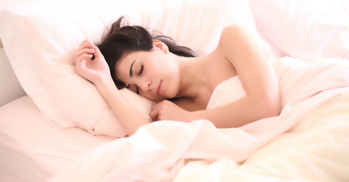Fair skinned woman with dark brown hair, sleeping in a bed with ivory sheets and pillows.