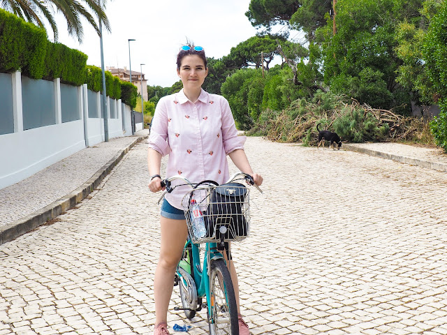 Me wearing denim shorts and pink shirt and shoes with a bike on the street. I also have a plastic water bottle and black bag pack in the front basket of my bike.
