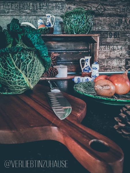 Im Vordergrund ein Wirsing auf Holzbrett. Im Hintergrund eine Porzellanschuessel im Design eines Wirsings