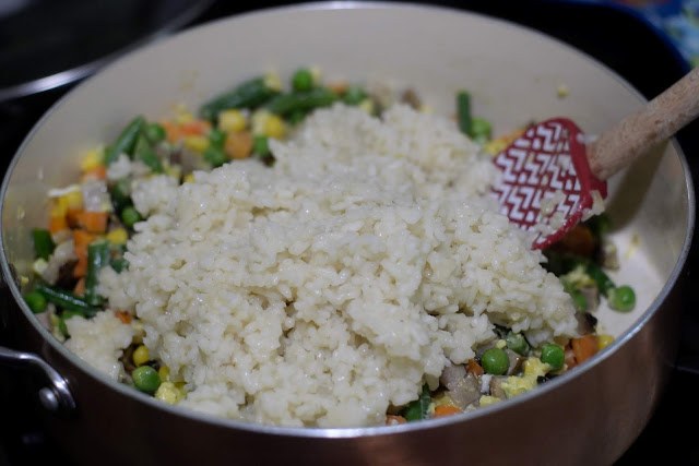 The cooked rice being added to the pan with the diced pork, egg, and vegetables.