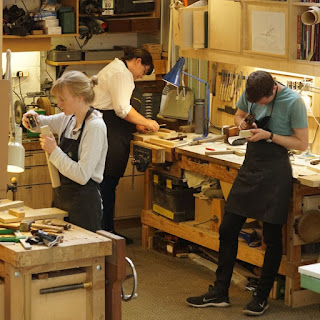 Image of three people in woodwork workshop