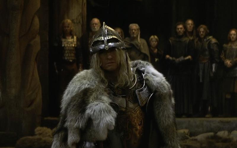 Fotograma de la película El guerrero nº 13, en el que se ve un vikingo rubio vistiendo pieles y portando un casco de metal, plateado.