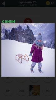 Девочка розовом пальто зимой с горы везет за собой санки