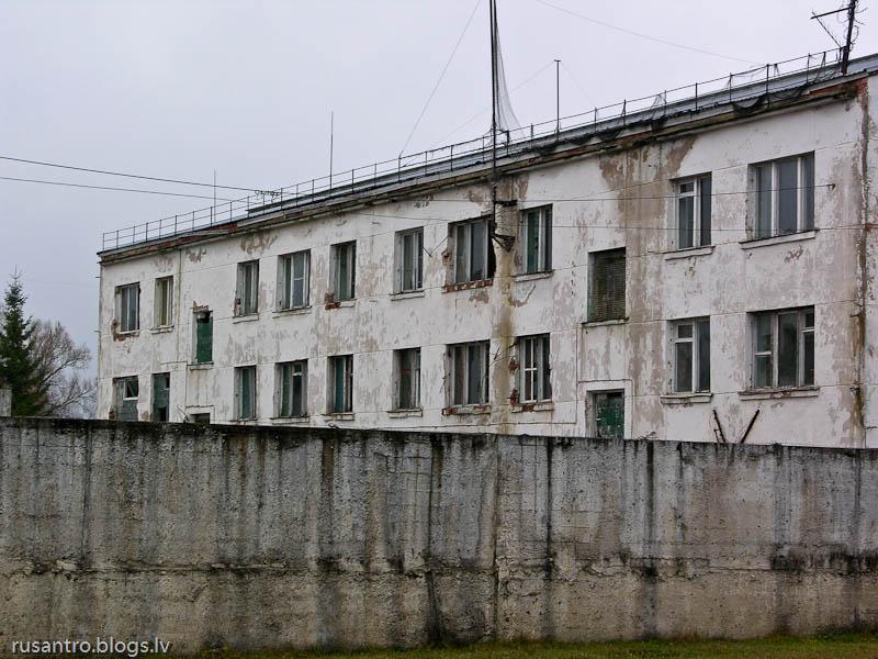 Apbružāta betona ēka aiz žoga ar dzeloņstieplēm