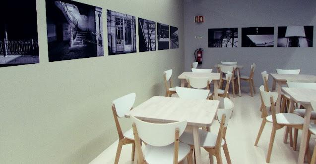 Mesas e cadeiras e fotografias na parede do antigo Mercado do Bolhão