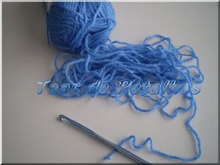 Foto mostrando fios utilizados em um trabalho de crochê e uma agulha de crochê com gancho.