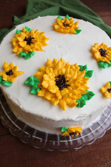 cake frosted in white buttercream with frosting sunflowers piped on top