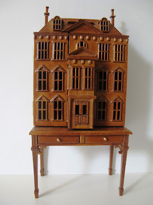 Dolls' house miniature wooden dolls' house mounted on a desk.