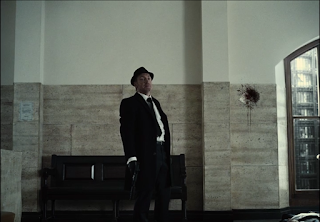 A terrorist in a black suit and hat stands next to a spot in the wall with a circular crack and a thick smear of blood.