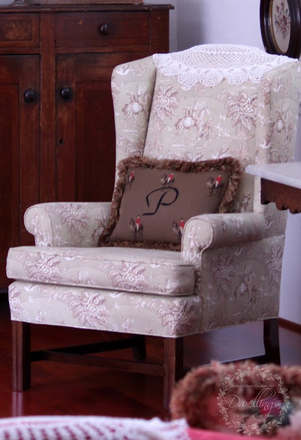 The camelback chair is upholstered in a hunt scene toile with an emroidered pillow.