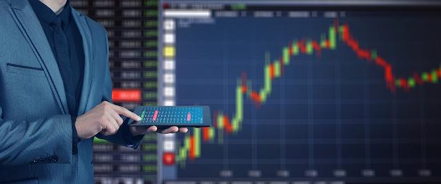 Osoba z tabletem dokonuje transakcji online, w tle wykres giełdowy