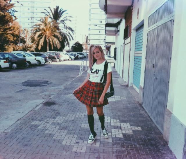 Alejandra Colomera vestida con camiseta blanca con mensaje, falda de tablas cuadros escoceses, tirantes, calcetas y zapatillas