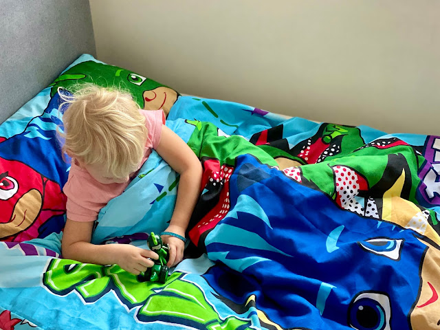 Child in a bed with PJ Masks duvet and pillow cover playing with a gecko toy