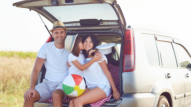 Mom, Dad, and daughter sitting in the back of car