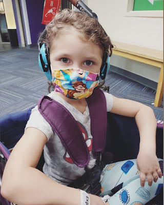 A little blonde-haired girl sitting in a purple wagon stroller, with a face mask on that has Disney Princesses on it, and wearing blue headphones.