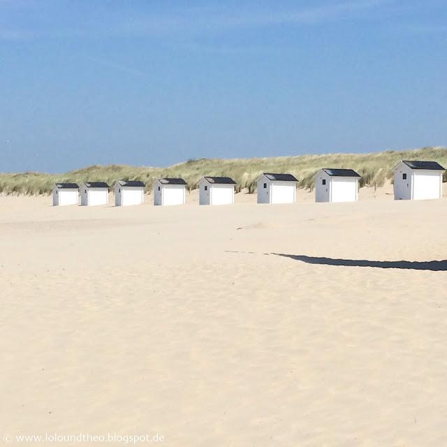 Weiße Strandhütten vor Düne