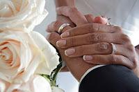 Sposi mano nella mano con le fedi ed un mazzo di rose
