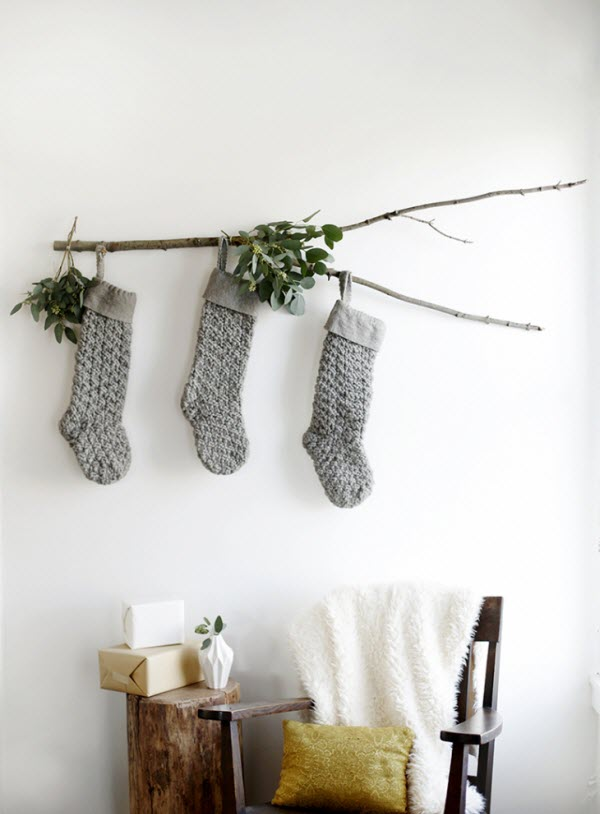 minimalist Christmas grey knit stockings hanging on branch