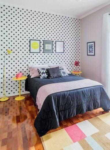quarto com cama de casal e papel de parede de bolinhas branco e preto