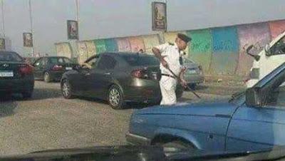 عقيد يمسك مكنسة لتنظيف احد الطرق بالقاهرة