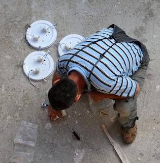 Bekir working outside on the light fittings