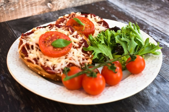 Vegan sesame bagel pizzas on a white plate with salad leaves and cherry tomatoes