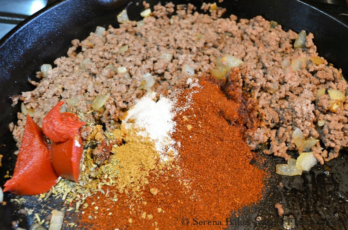 Cooked Ground Beef, Garlic, Chili Powder, Tomato Paste, Cumin, Oregano, and salt in a cast iron skillet to make Ground Beef Enchilada Filling.