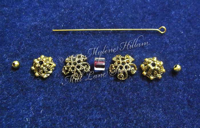 A selection of gold bead caps arranged in order from small to large to small