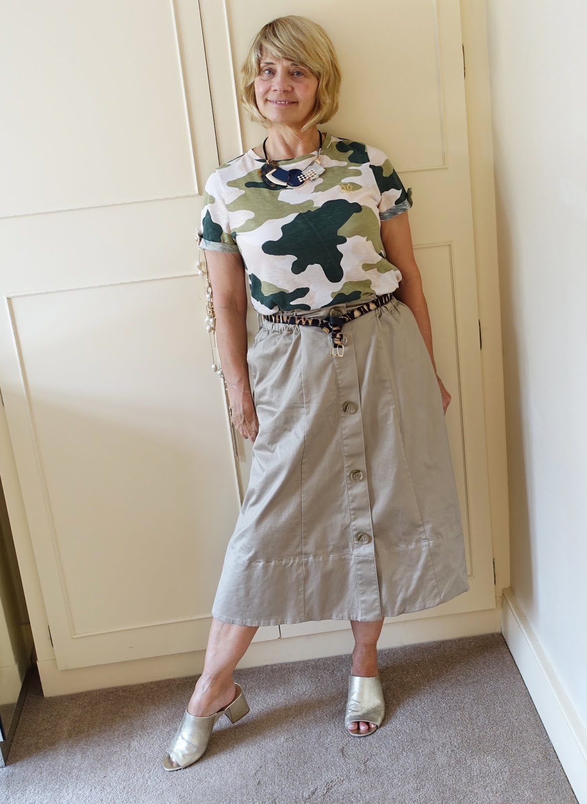 A casual work look: camo tshirt and midi skirt with gold mule sandals