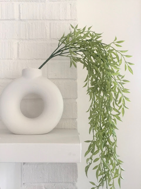 white textured modern donut vase with faux greenery vine