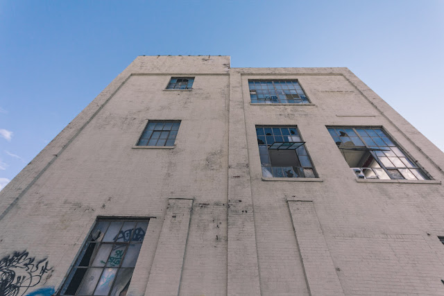 side of an abandoned building with open windows