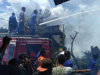 Petugas pemadam kebakaran berusaha memadamkan api yang membakar rumah pak kepling.